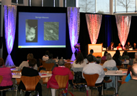 image of the event, showing a speaker with projection of cancer cells