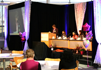 image of the event, showing a speaker, the panelists and audience