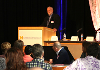 image of Max Wicha, MD, giving the opening address speaking with a participant