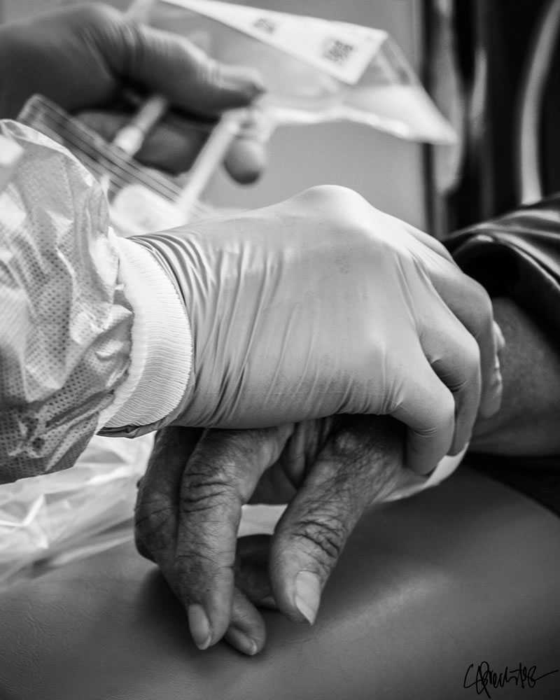 black and white image of the gloved hand of a care provider holding the hand of their patient